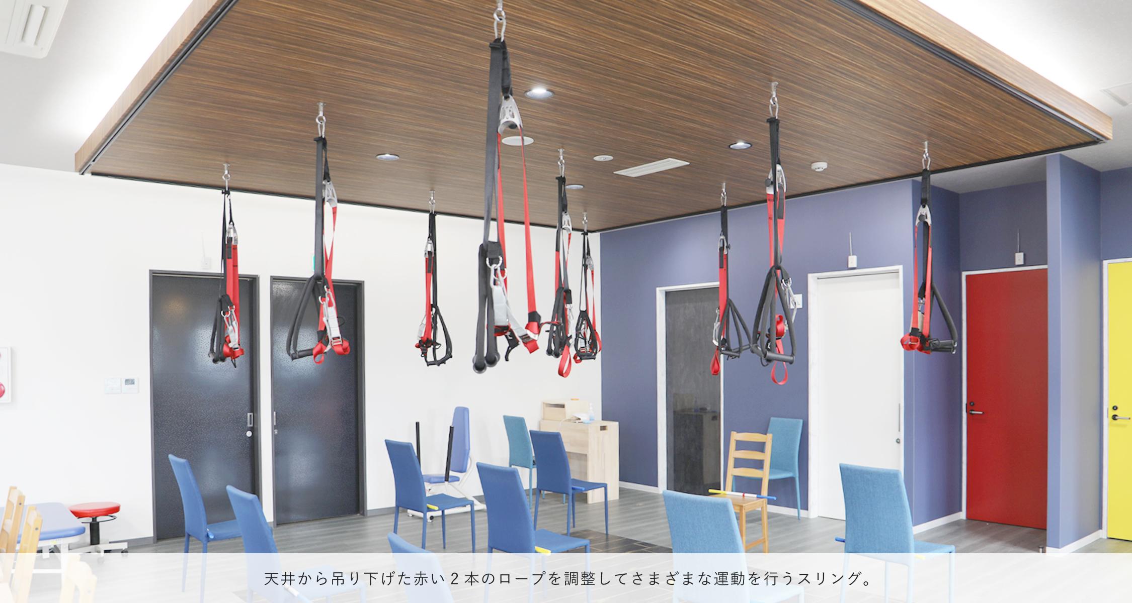 天井から吊り下げた赤い2本のロープを調整してさまざまな運動を行うスリング。